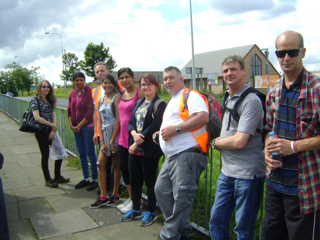 Image of nine smiling people stood in a row outside. They are a mix of men and women of different ages.