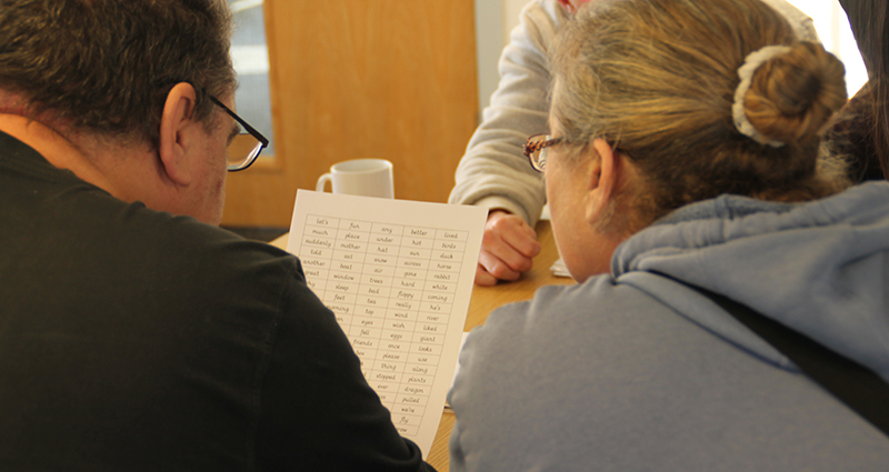 Photo of two people working through reading exercise.