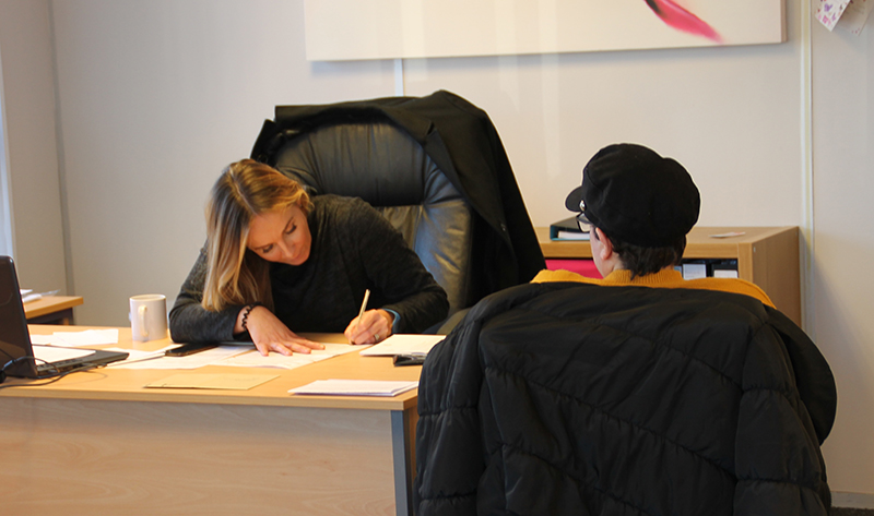 Photo of two people at desk. One woman is writing while the other watches.