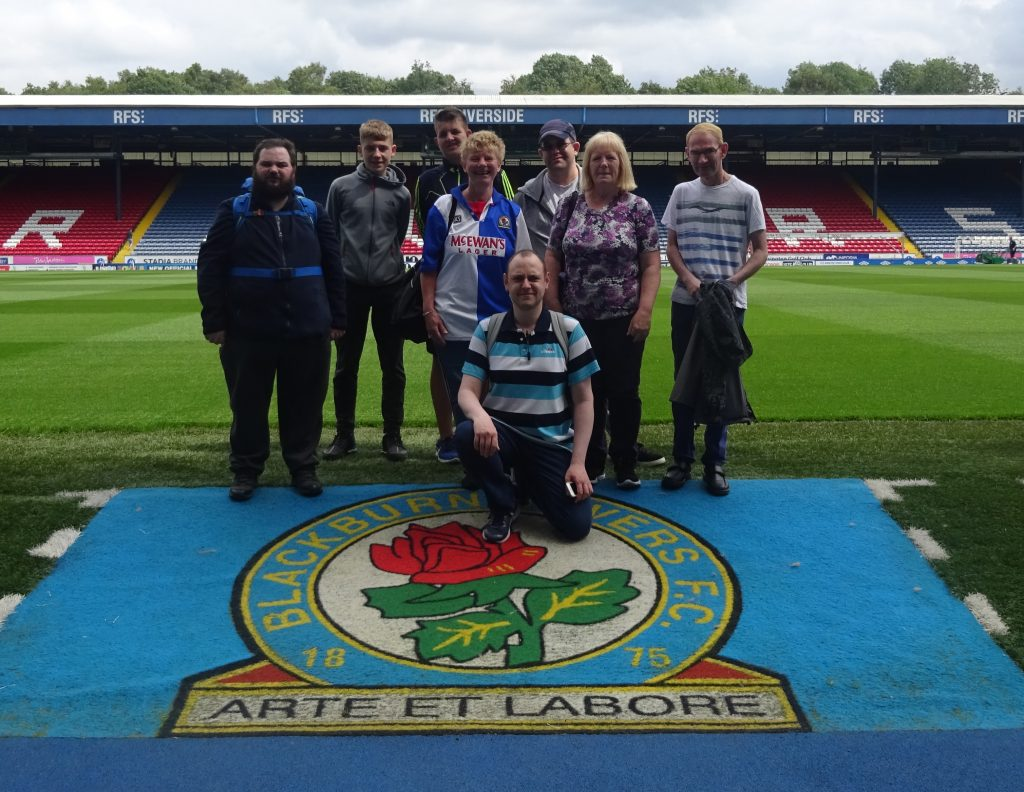Group of 8 people in front of Blackburn Rovers football pitch on top of the club's logo.